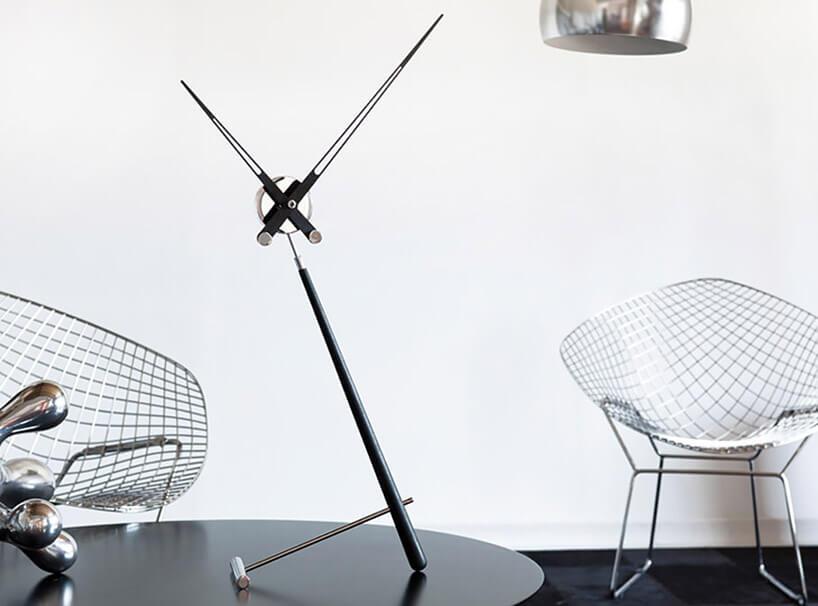 nietypowy zegar zzsamymi wskazówkami na czarnym stole