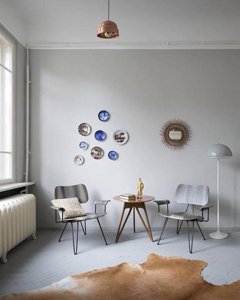 dwa krzesła wokół małego stolika na tle ściany zobrazkami na talerzach