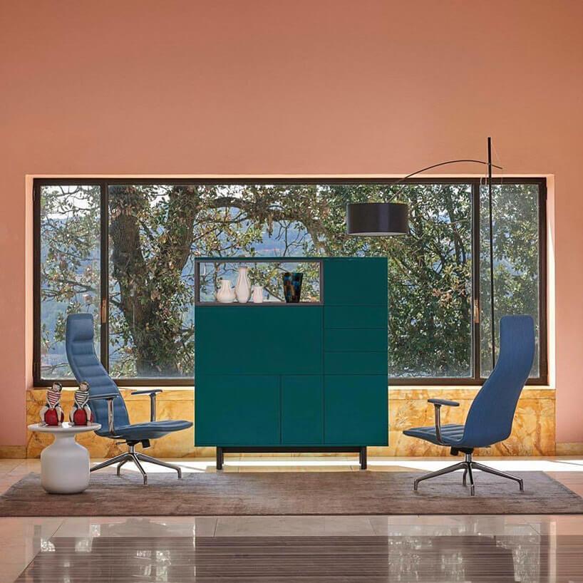 pomarańczowe wnętrze zdużą wolnostojące szafką idwoma fotelami