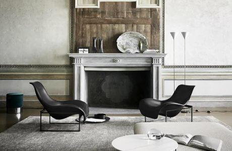 dwa niskie fotele we wnętrzu w starym stylu z imitacją kominka