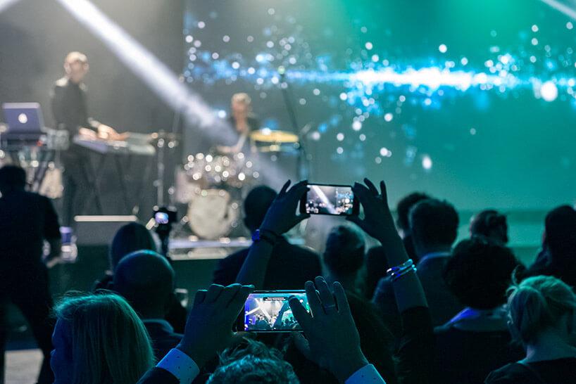 ludzie nagrywający koncert smartfonami na tle sceny