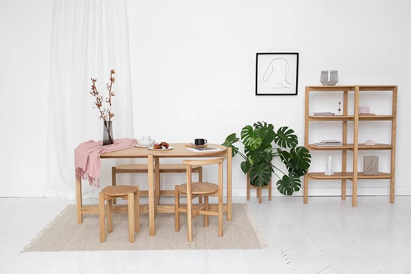 drewniane meble PIANO od Nudo designstóła złąweczką stołkiem ikrzesłem obok płytkiej szafki zpółkami