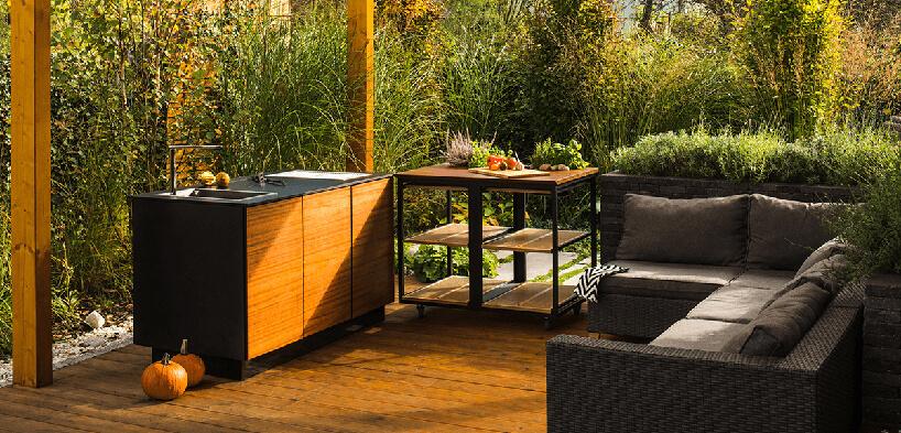 drewniane patio zciemną szafką ze zlewem przy czarnej szafce na kółkach na tle wysokich roslin wogrodzie