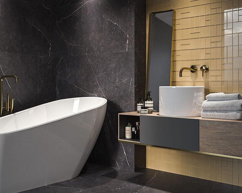 aranżacja łazienki zpłytkami Verde Garden, Gold Mix od Ceramika Paradyż ze stojącym lustrem na szafce wiszącej obok białej wanny