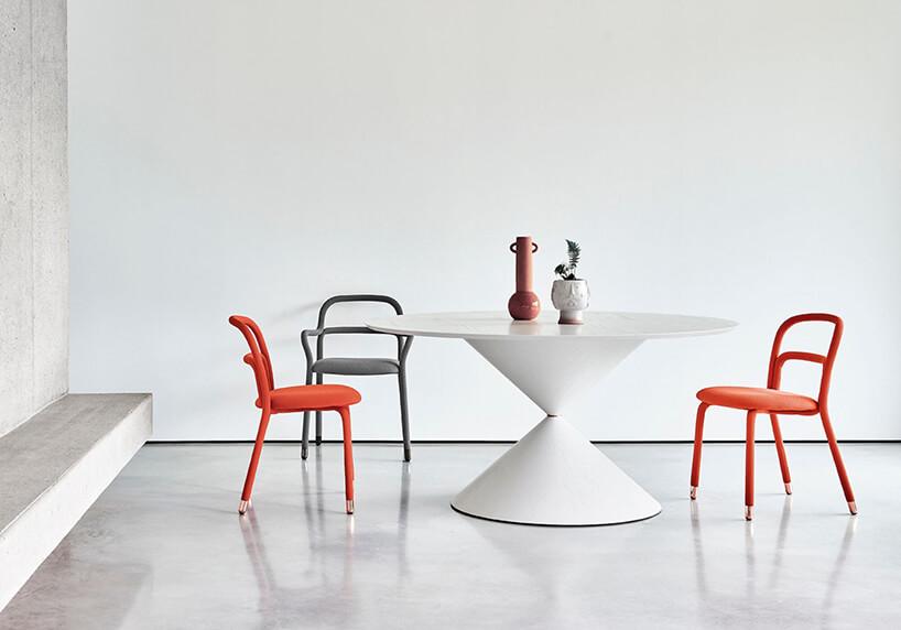 biały okrągły stół Clessidra od Mid wotoczeniu dwóch pomarańczowych ijednego białego krzesła wbiałym pomiszeczeniu