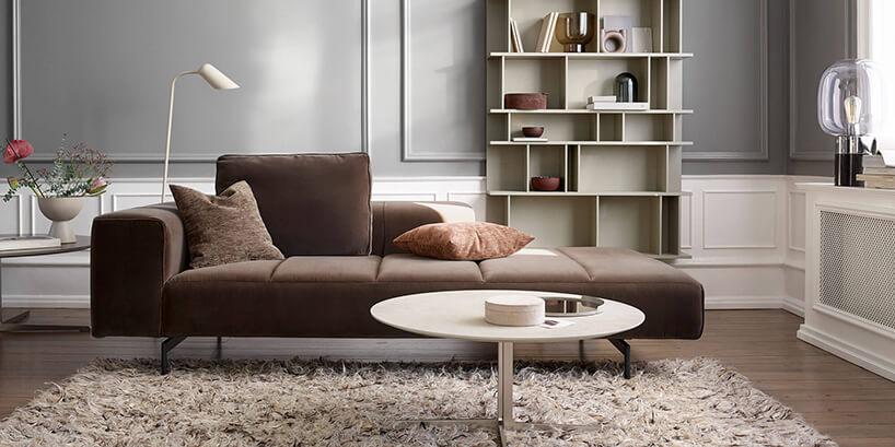 brązowa sofa Amsterdam od BoConcept waranżacji salonu na tle szarej ibiałej ściany
