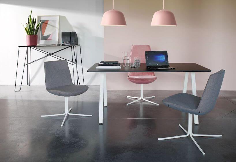 kolekcja Lumi od Bejot szare iróżowe krzesła na białej nodze przy biurku zciemnym blatem pod różowymi lampami