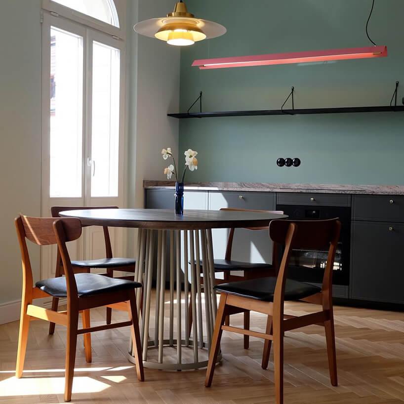prosta elegancka kuchnia zduzym okrągłym stołem zdrewnianym blatem zczterem krzesłami