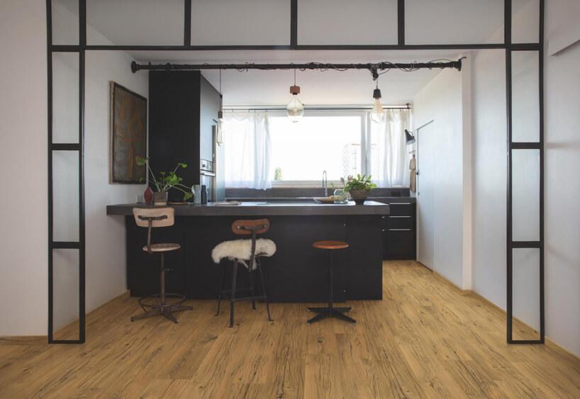 elegancka jasna kuchnia zczarnymi meblami idrewnianą podłogą