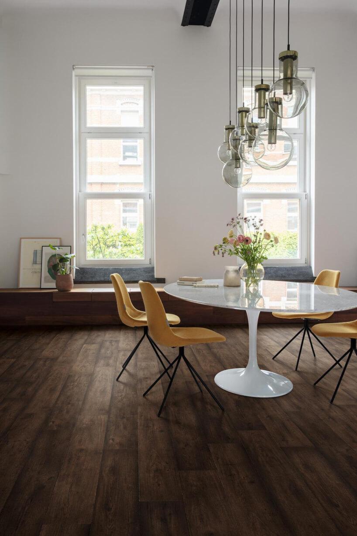 aranżacja jasnego wnętrza zciemną podłogą białym błyszczącym stołem iczterema bezowymi krzesłami