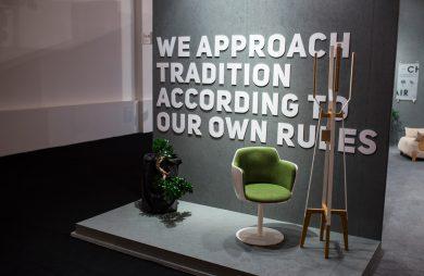 szara prezentacja z zielonym fotelem białym wieszakiem na tle białego napisu w języku angielskim