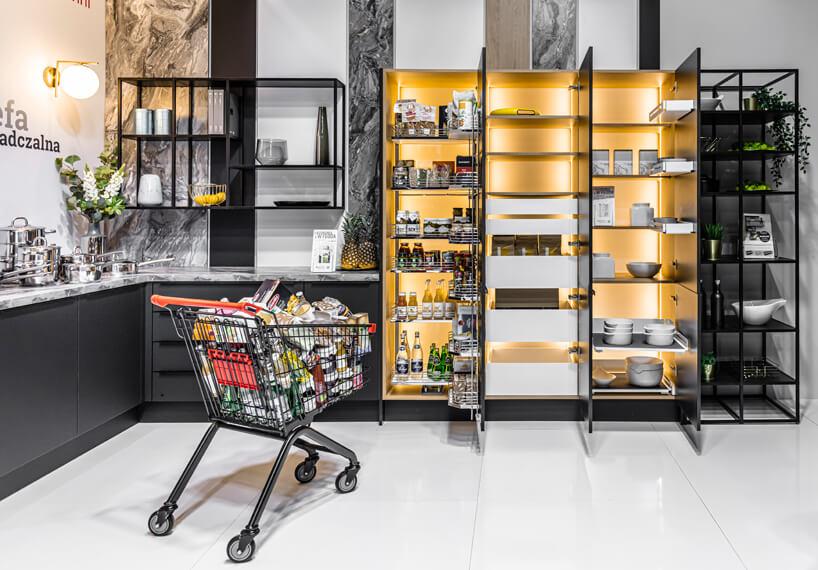biało czarne stoisko PEKA podczas Warsaw Home 2019 systemuy półek wczarnych meblach obok obłożonego wózka sklepowego