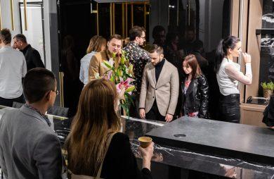 odwiedzający na stoisku Stoisko ernestrust podczas Warsaw Home 2019 dookoła czarnej wyspy z kamiennym blatem
