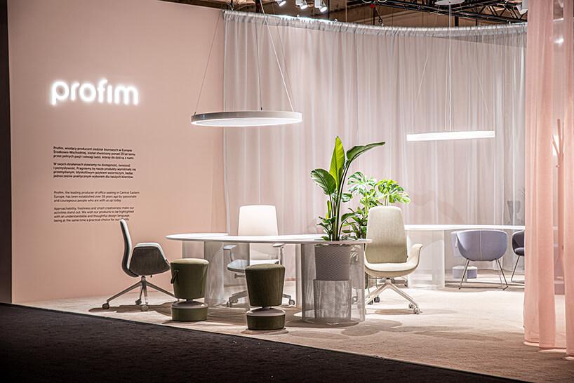 stoisko Profim na Warsaw Home 2019 nowoczesne białe biurko zdwoma jasnym fotelami na kółkach idwóch wyjątkowych puf