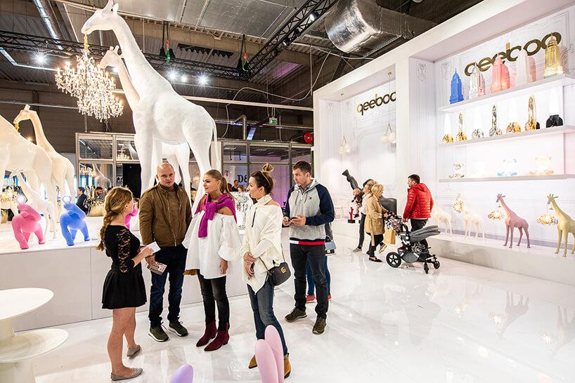 odwiedzający Warsaw Home 2019 pośród białych stoik ibiałych żyraf od qeeboo