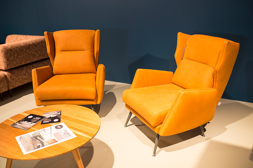dwa pomarańczowe fotele na stoisku ARIS CONCEPT podczas Warsaw Home 2019 przy okrągłym drewnianym stoliku