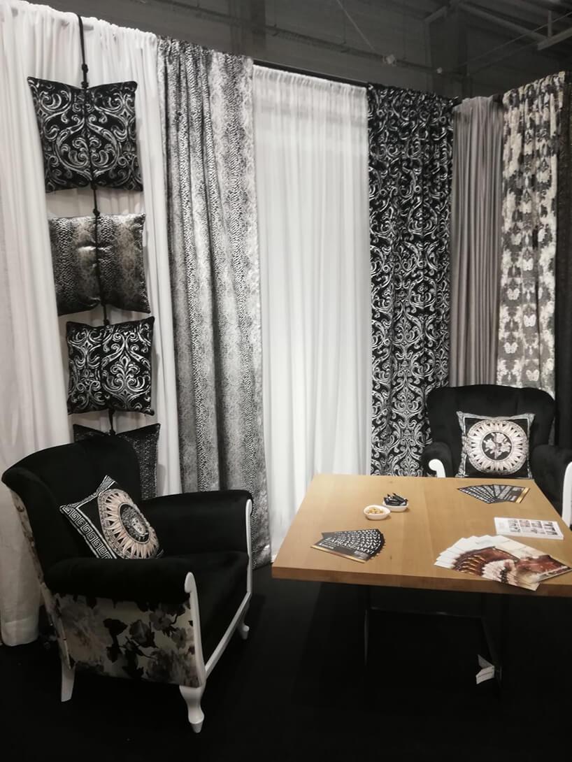 eleganckie stoisko RAD-POL podczas Warsaw Home 2019 dwa czarno białe fotele na tle eleganckich poduszek oraz firan izasłon