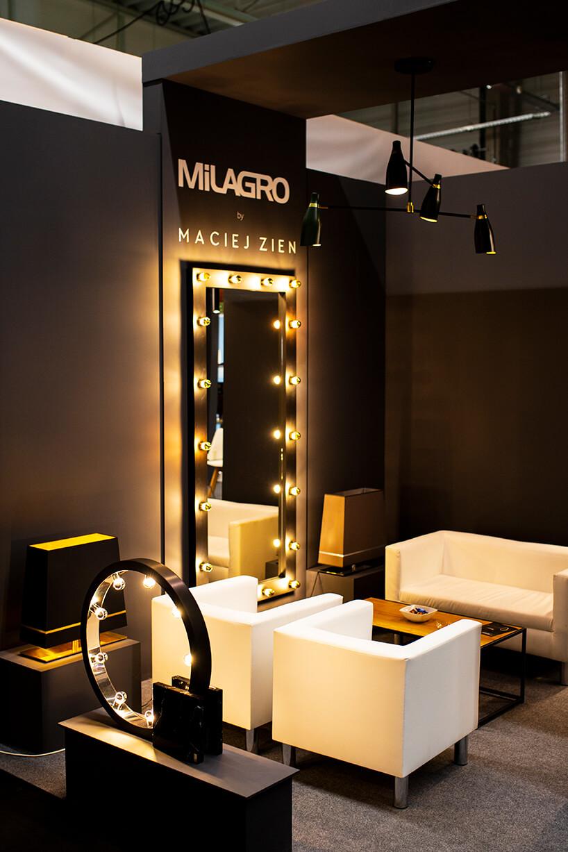 ekskluzywne oświetlenie na czarnym stoisku MiLARGO wotoczeniu otoczeniu czarnej małej sofy zdwoma fotelami