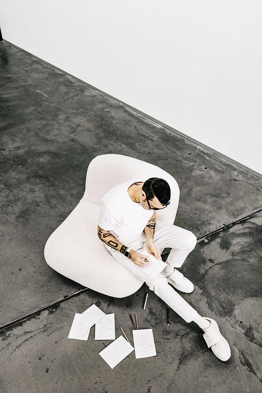 mężczyzna Karim Rashid siedzący na biały fotelu Chelsea na czarnej podłodze