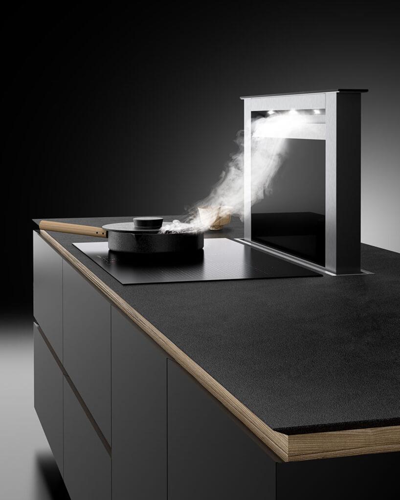 elegancki czarny okap Moondraft od Ciarko zamontowany wczarnej wyspie kuchennej przy indukcyjnie płycie