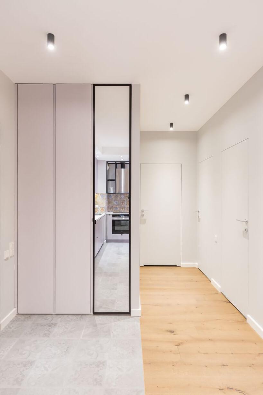 industrialne wnętrze mieszkania wWarszawie od Decoroom biały korytarz zukrytymi drzwiami