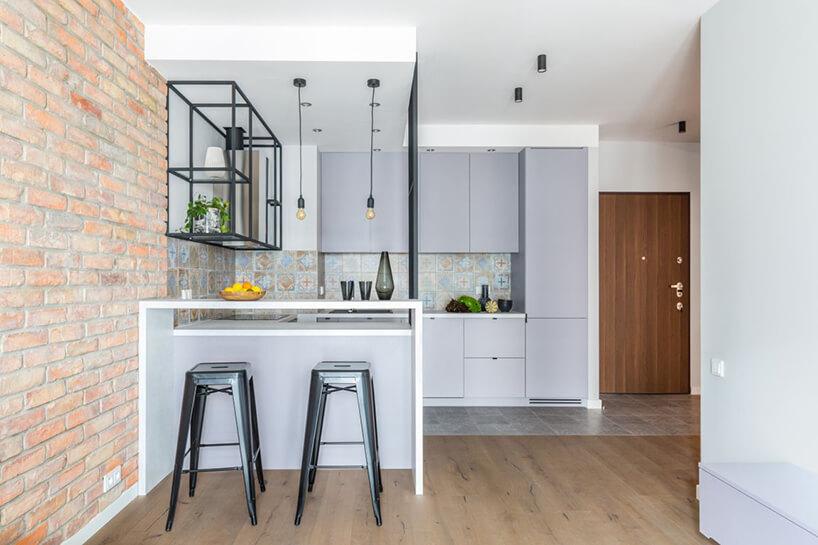industrialne wnętrze mieszkania wWarszawie od Decoroom widok zsalonu na białą kuchnię zczarnymi dodatkami