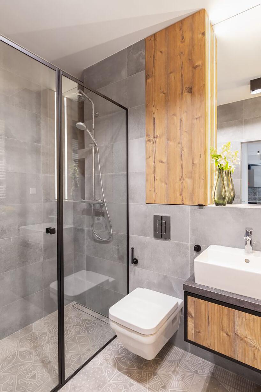 industrialne wnętrze mieszkania wWarszawie od Decoroom szara łazienka znatryskiem idrewnianymi wykończeniami zabudowy iszafki