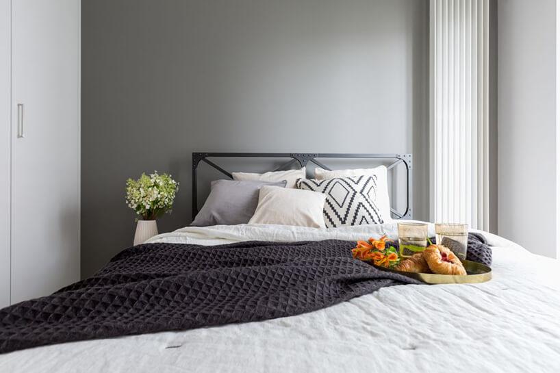 industrialne wnętrze mieszkania wWarszawie od Decoroom szara sypialnia zdużym łóżkiem zmetalowym czarnym zagłówkiem