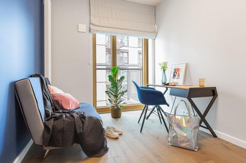 industrialne wnętrze mieszkania wWarszawie od Decoroom mały gabinet zmałym biurkiem iniebieskim krzesłem na drewnianej podłodze