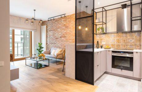 industrialne wnętrze mieszkania w Warszawie od Decoroom- salon połączony z kuchnia biała wyspą
