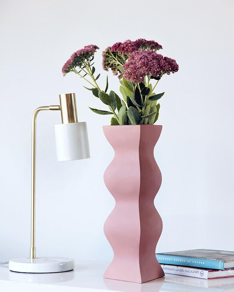 różowy wazon opowycinanym kształcie zkwiatami obok białej lamki ze złotym ramieniem