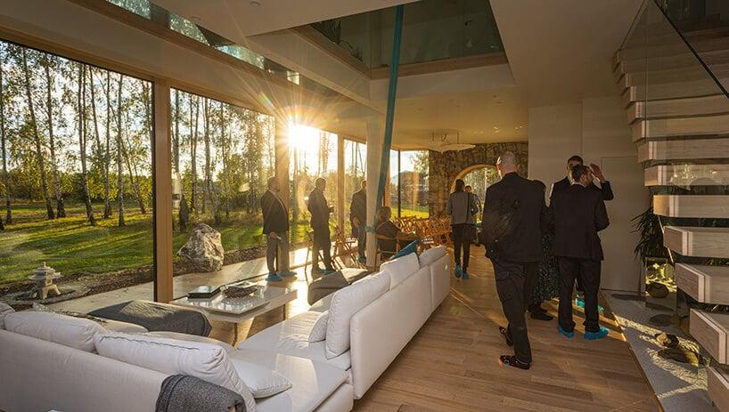 wnętrze domu pasywnego zdużym białym stołem oraz gośćmi