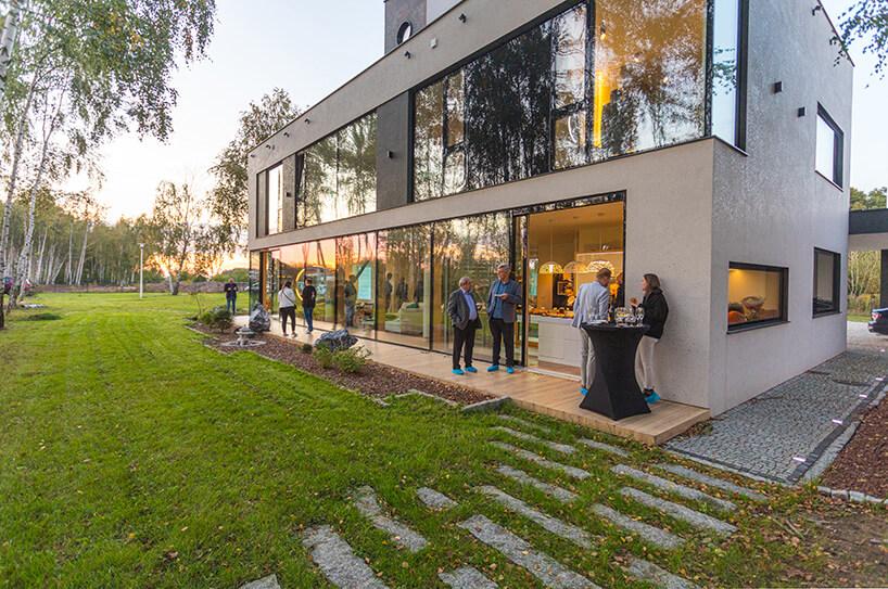 duży pasywny dom zprzeszkleniami oraz wystawnym bankietem oraz zielonym gęstym trawnikiem na posesji