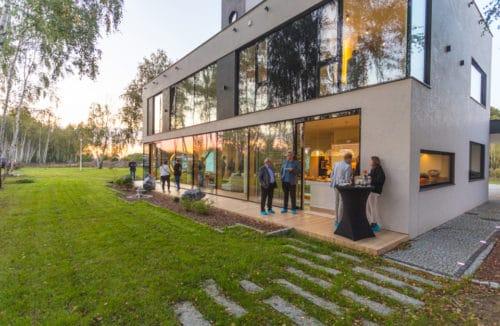 duży pasywny dom z przeszkleniami oraz wystawnym bankietem oraz zielonym gęstym trawnikiem na posesji
