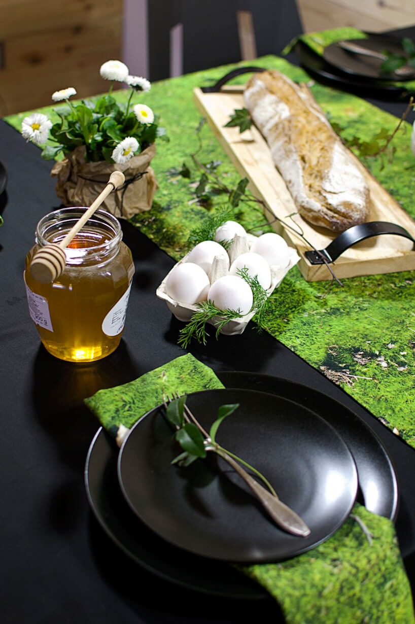 zastawiony stół wielkanocny zczarną zastawą ipodkładkami zmotywem trawy