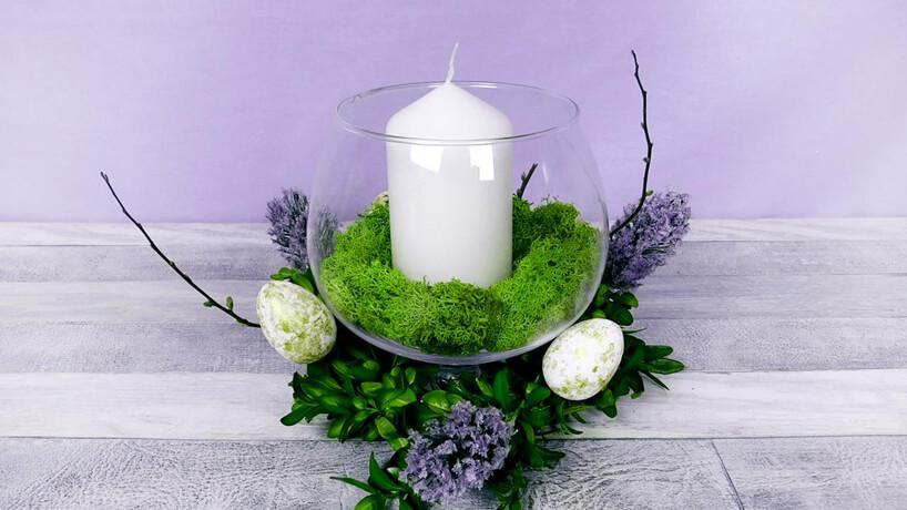 stroik wielkanocny ze szklanego wazonu zmchem iświecą wśrodku