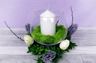 stroik ze szklanego wazonu z mchem i świecą w środku