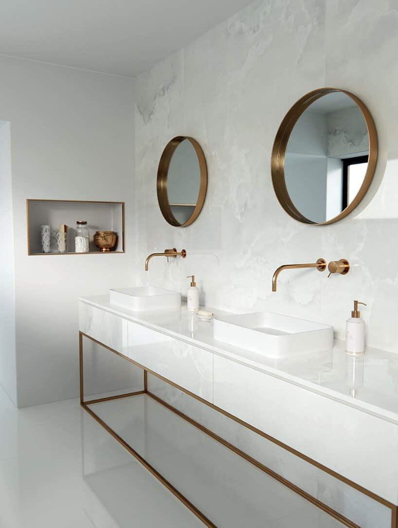 biały połyskujący blat na złotawej ramie włazience zokrągłymi lustrami na ścianie
