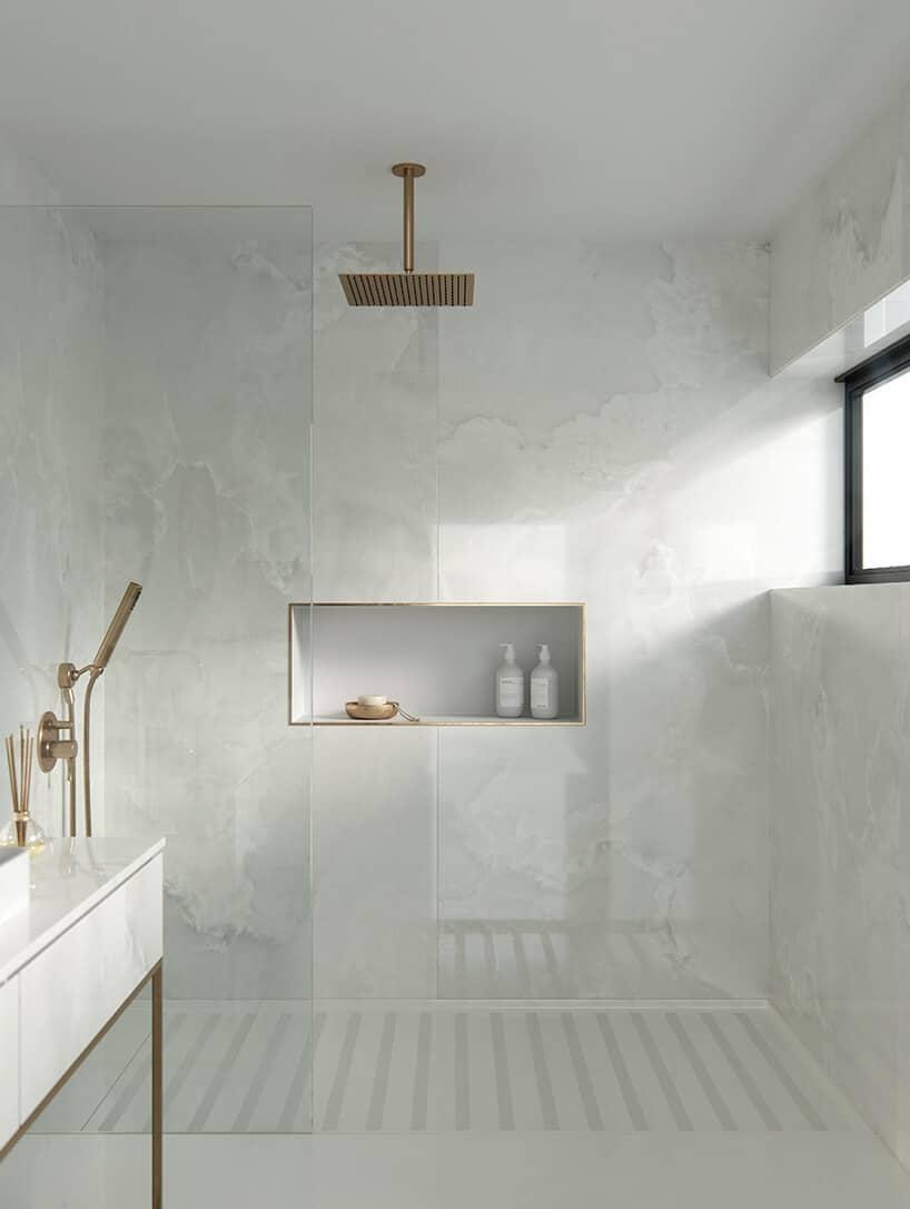 biało szara łazienka zmałym oknem oraz dodatkami armatury wkolorach brązu