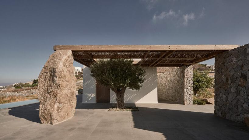 biały kamień podtrzymujący drewniany dach przy wejściu do willi zmałym drzewem oliwnym