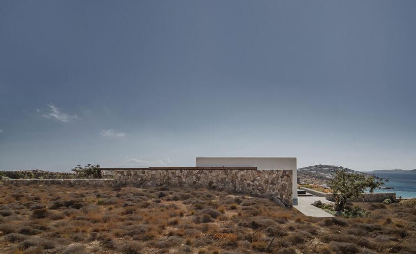 widok na kamienną ścianą chowającą się wzboczu greckiej wyspy