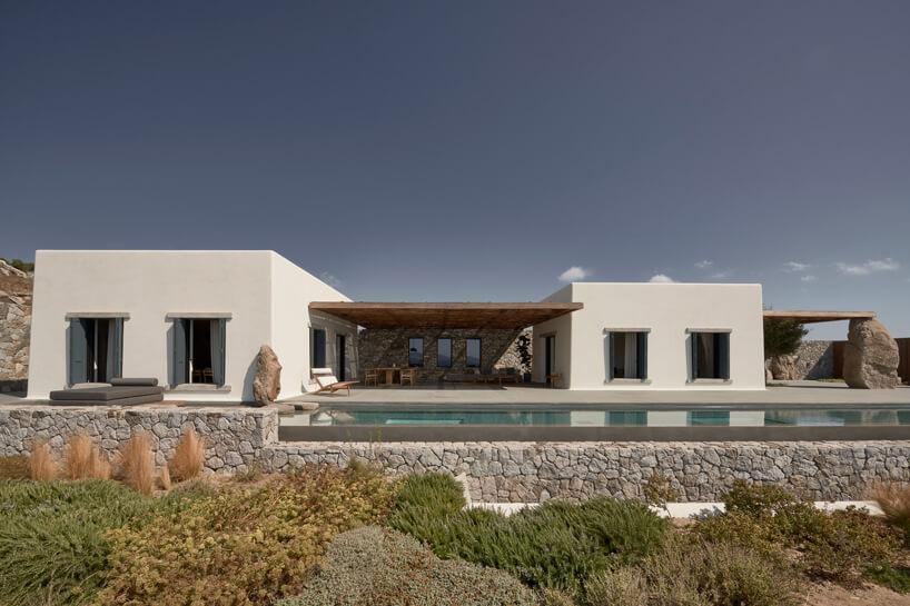 dwa białe budynki willi połączone tarasem zdrewnianym zadaszeniem nad brzegiem basenu