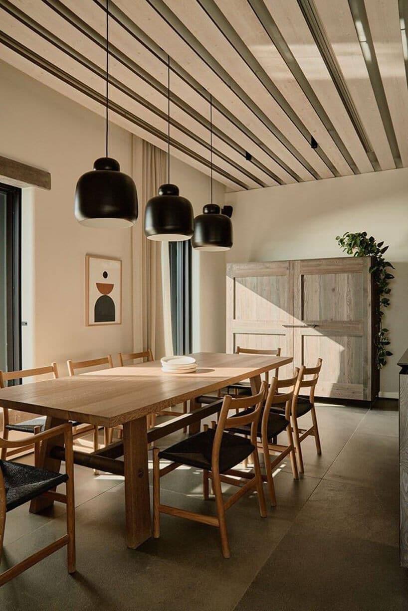 jasne wnętrze jadalni zciemną podłogą zdużym drewnianym stołem pod trzema czarnymi lampami