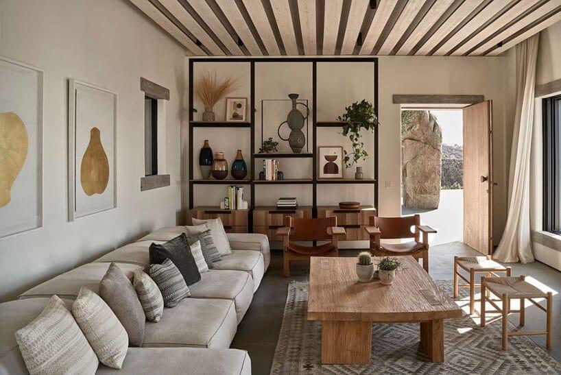 jasne wnętrze salonu zdługą jasną sofą przy niskim drewnianym stoliku