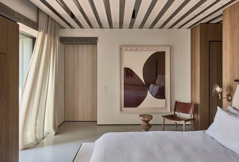 jasna sypialnia gościnna zkamienną podłogą zdrewnianą zabudową