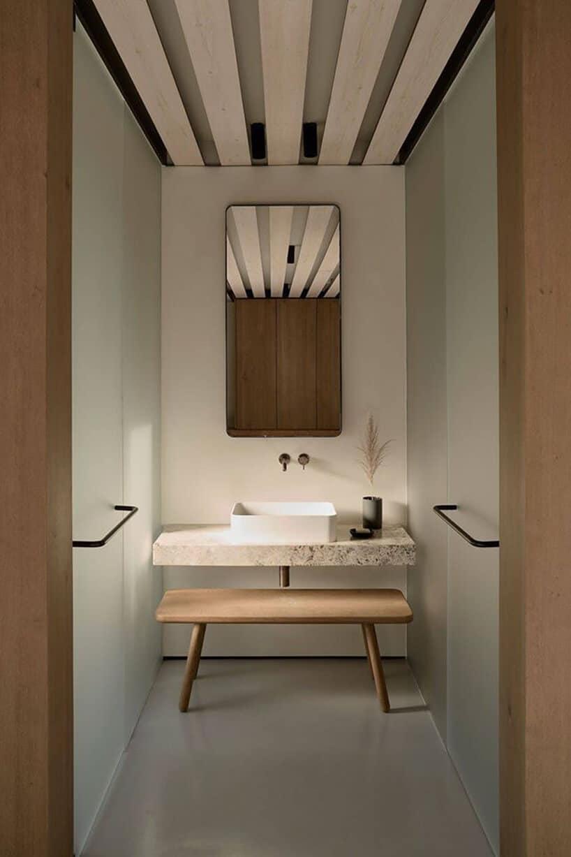 jasna mała łazienka zbiałą umywalką na kamiennym biało czarnym blacie