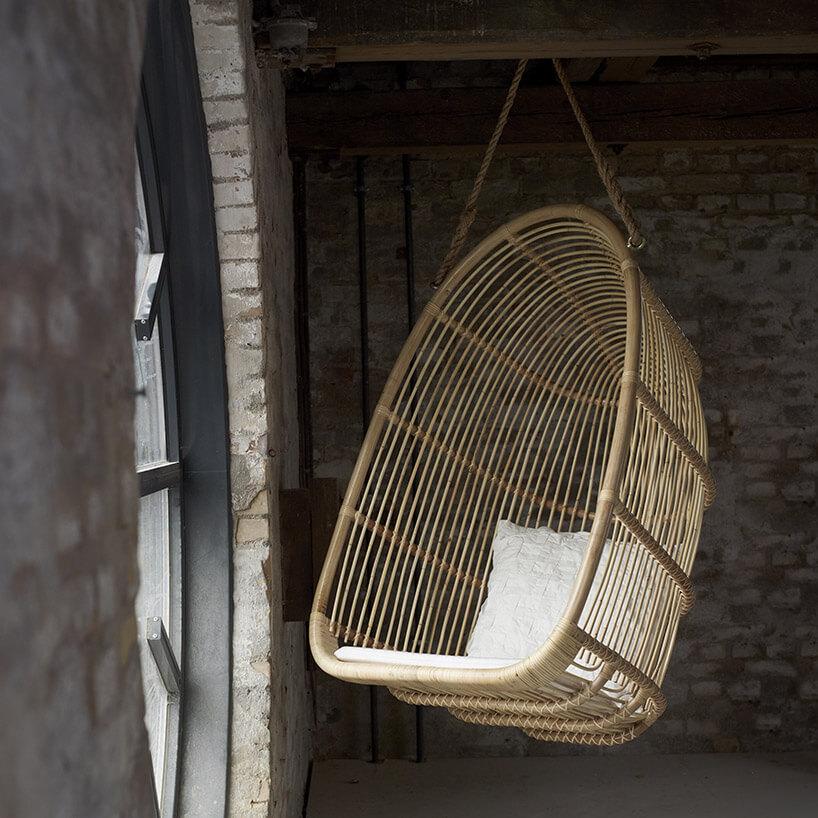 jasny wiklinowy fotel wiszący przy duzym okrągłym oknie