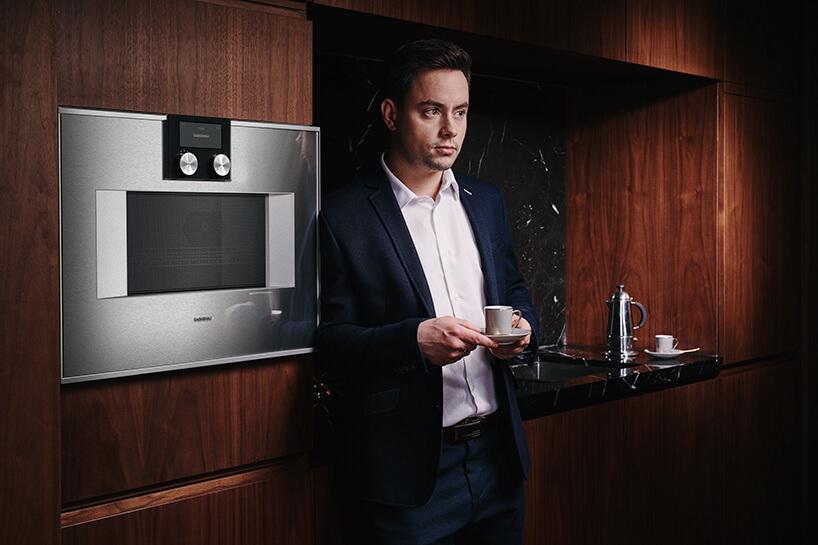 mężczyzna wgranatowym garniturze zfiliżanką kawy oparty obrązową zabudowę kuchenną ze srebrnym piekarnikiem Gaggenau
