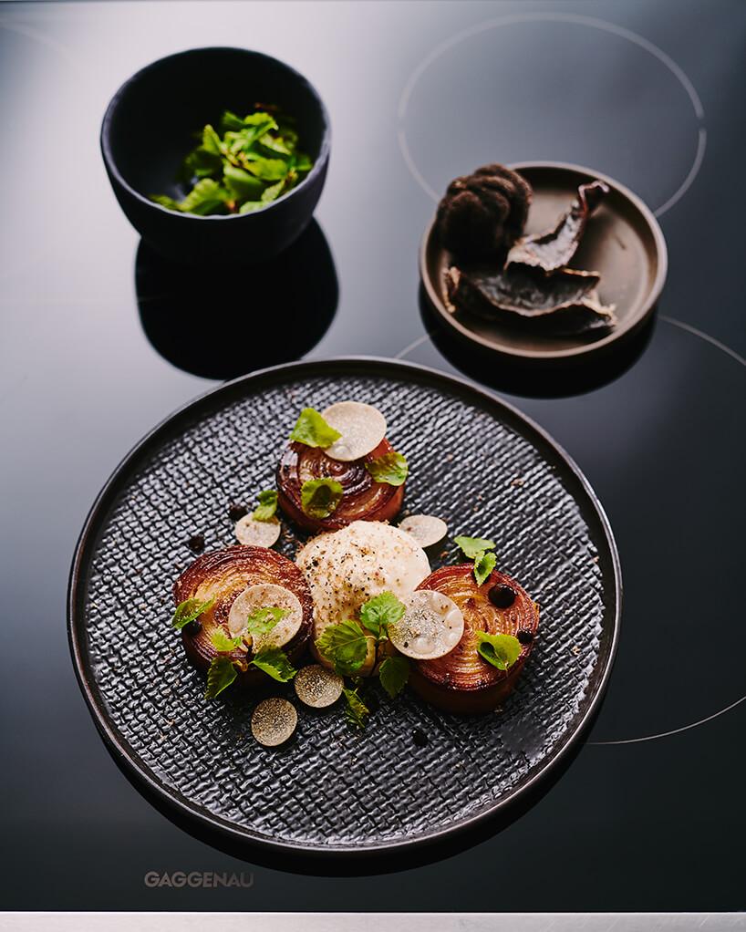 elegancki danie na ciemnym talerzu obok miseczki zzielonymi listkami stojącego na czarnej płycie indukcyjnej Gaggenau
