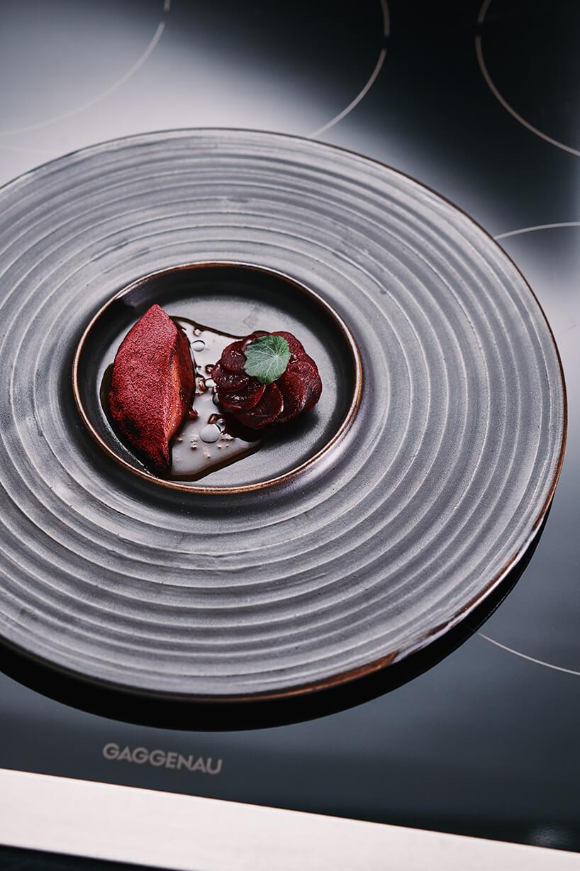 elegancki deser na ciemnym talerzu stojącego na czarnej płycie indukcyjnej Gaggenau